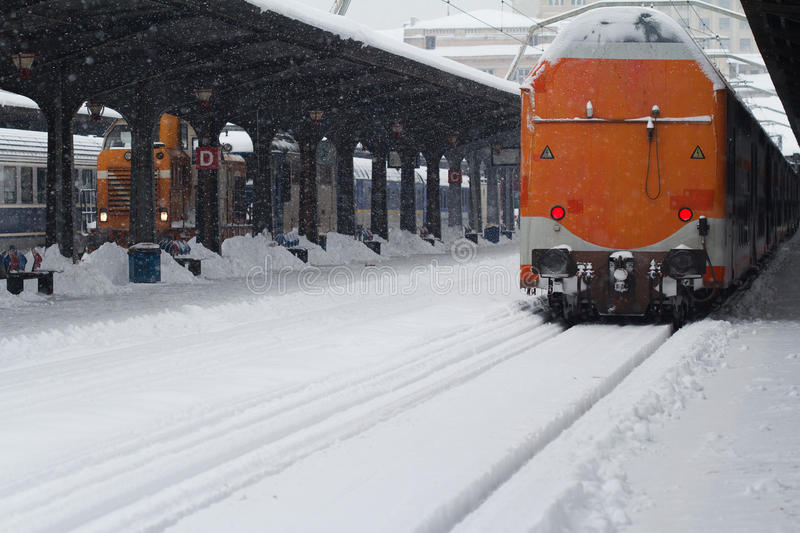 Rear view of train in railway station in winter time. Rear view of the back of an orange passenger train covered in snow stopped in railway station, winter time royalty free stock photos