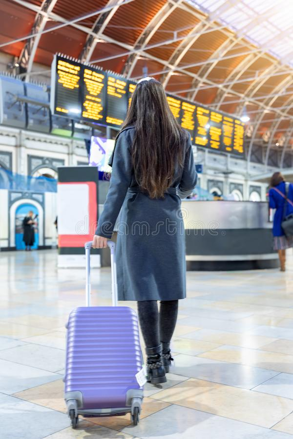 Traveler woman on a busy train station looking at the timetable screens. Rear view of a traveler woman with luggage on a busy train station looking at the royalty free stock photography
