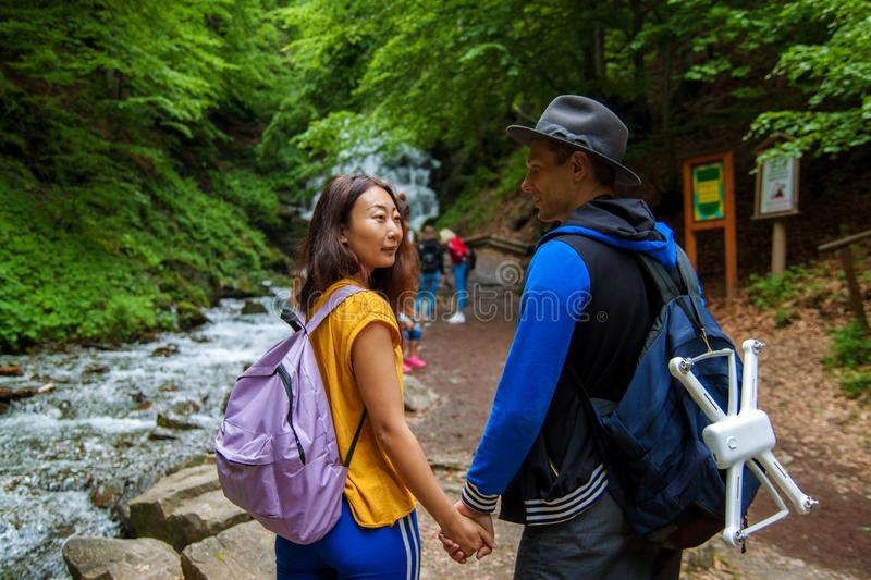 A young couple crossing a mountain stream while out walking together. Travelers stand near waterfalls. Rear view of travelers with backpacks are standing in the stock images