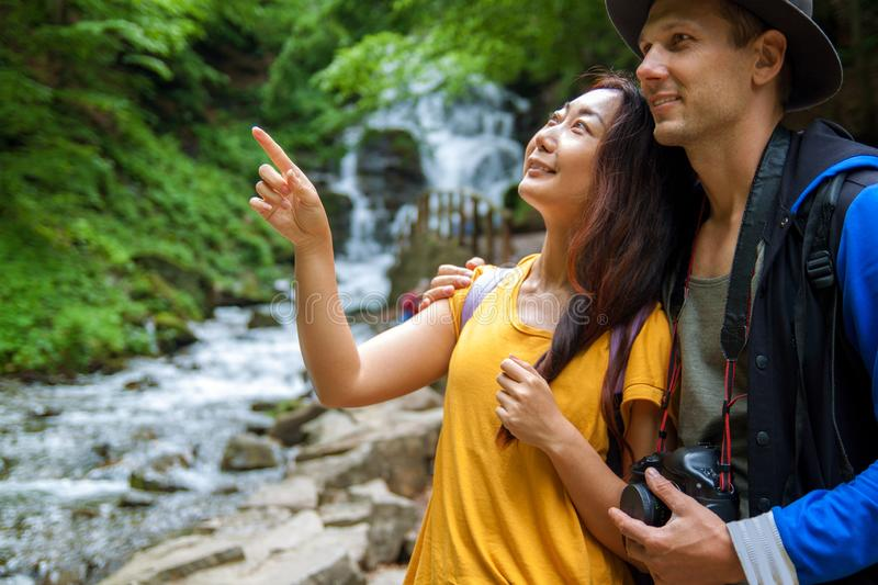 A young couple crossing a mountain stream while out walking together. Travelers stand near waterfalls. Rear view of travelers with backpacks are standing in the royalty free stock images