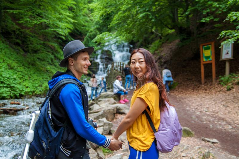 A young couple crossing a mountain stream while out walking together. Travelers stand near waterfalls. Rear view of travelers with backpacks are standing in the royalty free stock photography