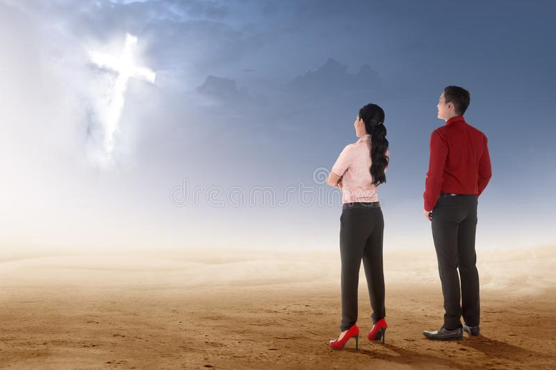 Rear view of two asian business people standing on desert and looking at glowing christian cross royalty free stock photos