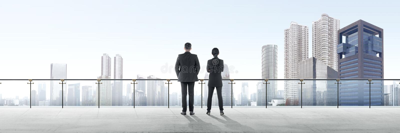 Rear view of two asian business people standing on modern terrace and looking at view royalty free stock photography