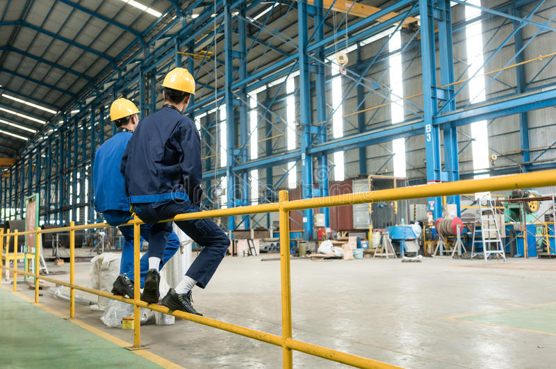 Rear view of two blue-collar workers during break stock photos