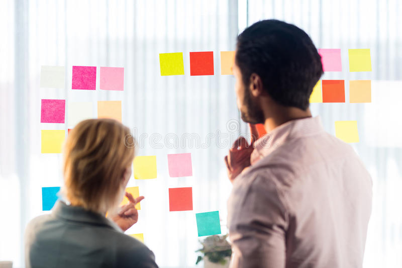 post business office. Download Rear View Of Two Business People Looking At Post It Wall Stock Image - Office