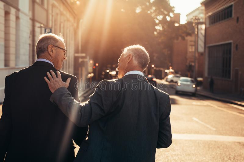 Two senior business people walking outdoors royalty free stock images