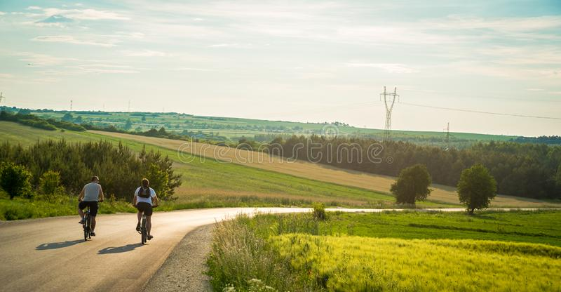 Rear view of two cyclists riding down the country road through mountains. Casual men having fun cycling down the empty road royalty free stock photography