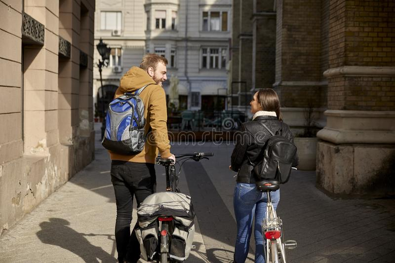 Rear view, two friends talking and walking in a street, pushing their bicycles on a street in a city royalty free stock image