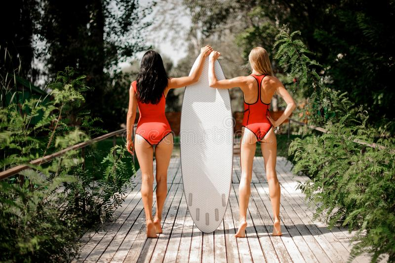 Rear view two girls standing on the two sides of the wakebo. Rear view two girls, blonde and brunette, in red swimsuits standing on the two sides of the white stock photo