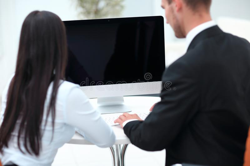 Rear view.two successful employee sitting behind a Desk. Photo with copy space royalty free stock photo