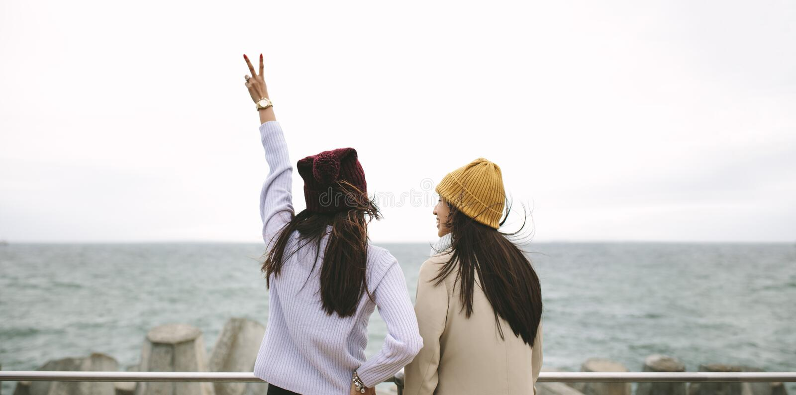 Rear view of two women standing together outdoors royalty free stock photos