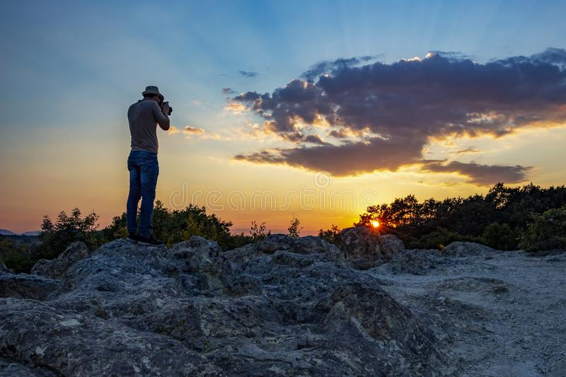 Rear view of unrecognizable male photographer taking pictures of the sunset over the Stone Mushrooms near Beli Plast village, stock images