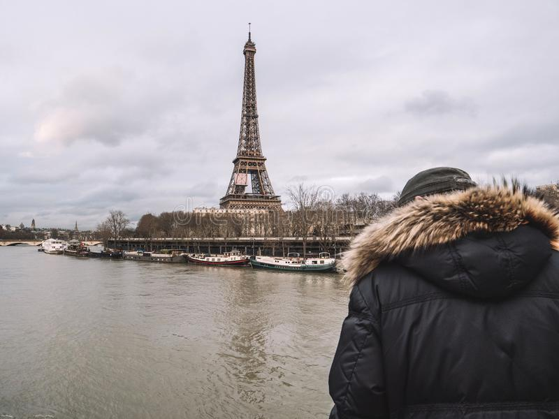 Parisian French man watching the flooding swollen Seine river. Rear view of Unrecognizable Parisian senior man watch the swollen river Seine near the Eiffel royalty free stock images