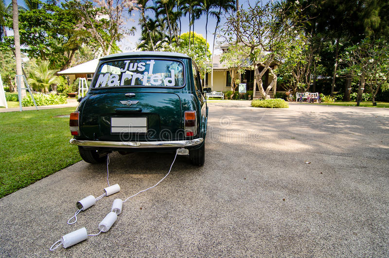 Rear view of a vintage car with just married sign and cans attached and beautiful landscape. Rear view of a vintage green car with just married sign and cans stock photography