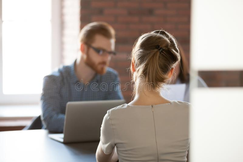 Rear view at woman applicant seeker at job interview concept royalty free stock image