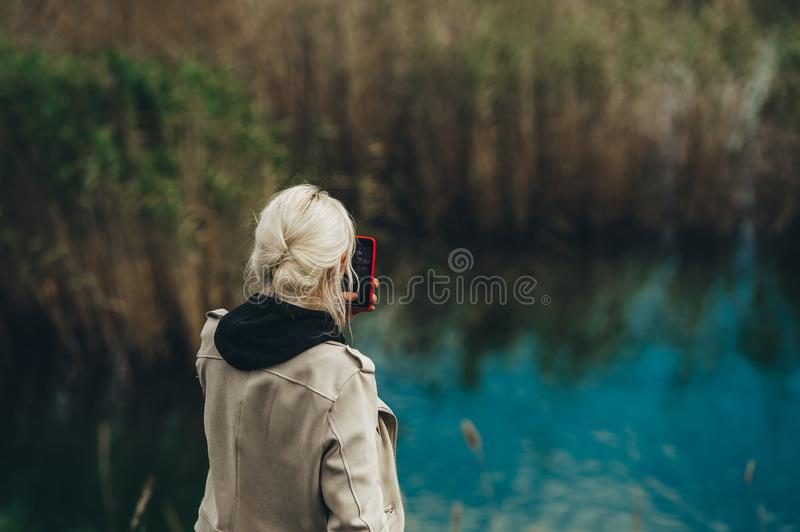Rear view of woman with blond hair taking photo of blue lake on mobile phone. Closeup royalty free stock image