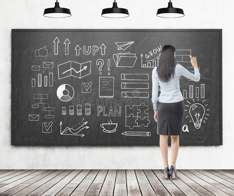 Rear view of a woman drawing a startup idea sketch on a blackboa. Rear view of a woman with black hair who is drawing a startup idea sketch on a blackboard royalty free stock photos
