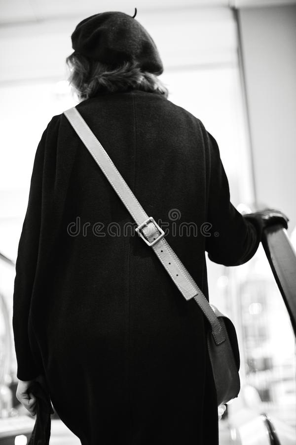 Rear view of woman on escalator. Stairs - black and white image royalty free stock photos