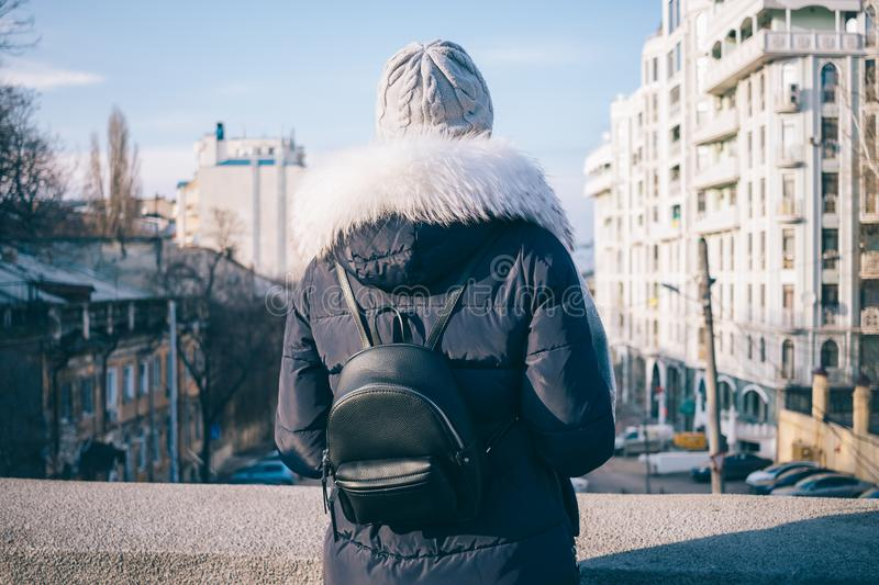 Rear view of woman looking at the city. From the bridge. Travel in the cold season, bright sun royalty free stock photo