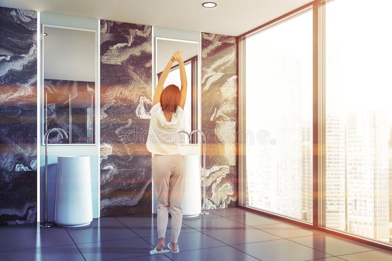 Woman in bathroom with double sink stock photos