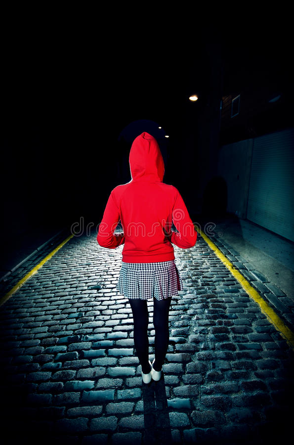 Rear View Of Woman In Red Hood On Street At Night stock images