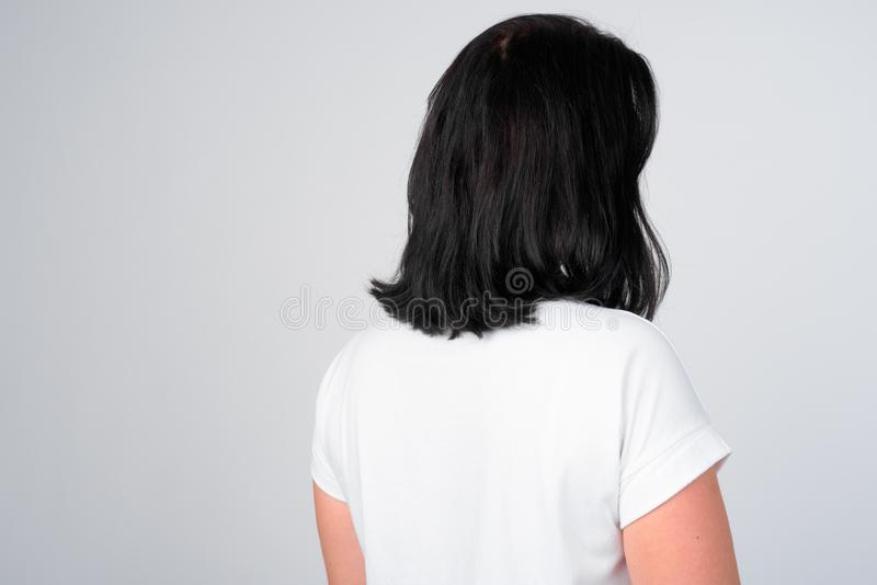 Rear view of woman with short hair against white background. Studio shot of beautiful woman against white background stock photography