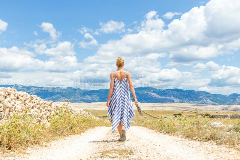 Rear view of woman in summer dress holding bouquet of lavender flowers while walking outdoor through dry rocky royalty free stock photo