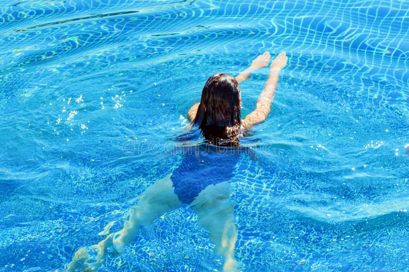 Rear view of a woman swimming. Swim and fitness royalty free stock photography