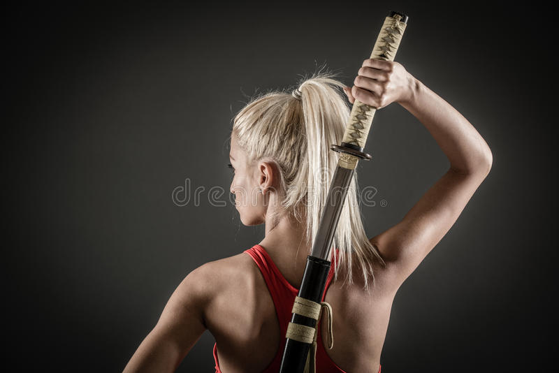 Rear View Of Woman With Sword. Pretty girl with a serious expression on her face drawing katana royalty free stock photos