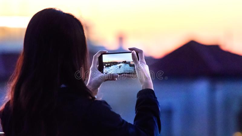 Rear view of a woman taking photos with her mobile of the Grand Canal in Venice, Italy royalty free stock photos