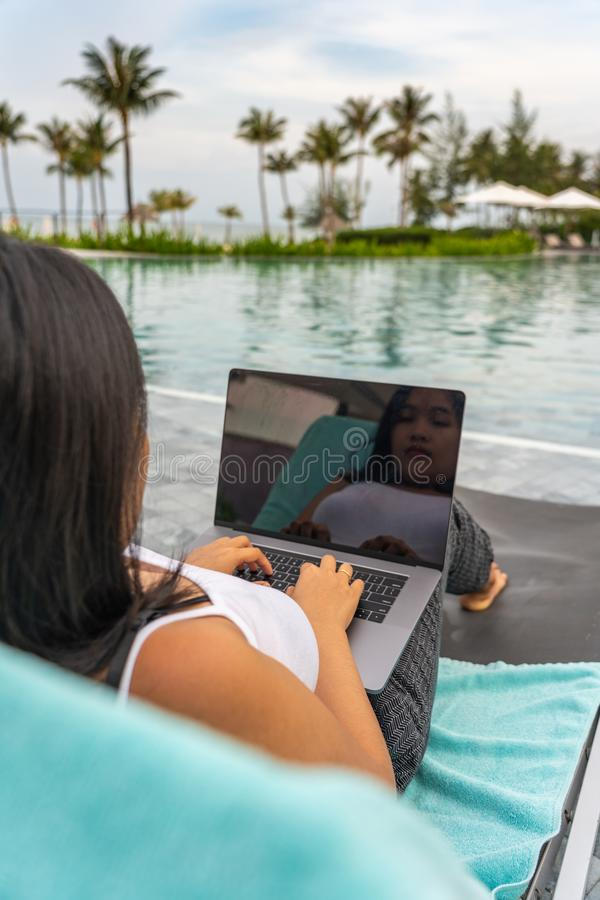 Rear view of woman using laptop at swimming pool royalty free stock photography