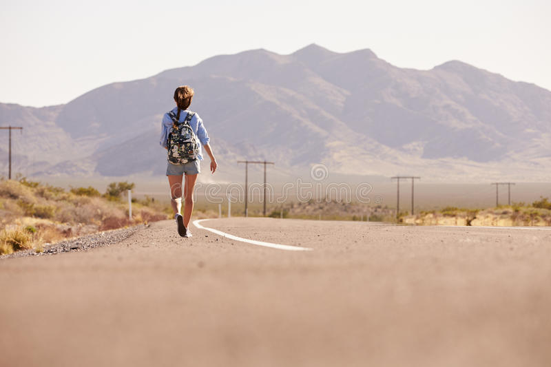 Rear View Of Woman On Vacation Hitchhiking Along Road royalty free stock photo