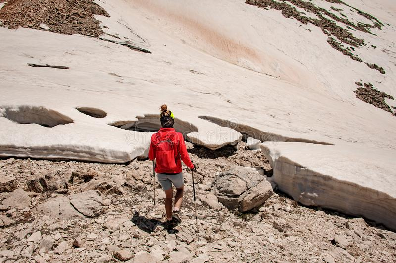 Rear view woman walking on the dirty snow and rocks with hiking sticks stock photography