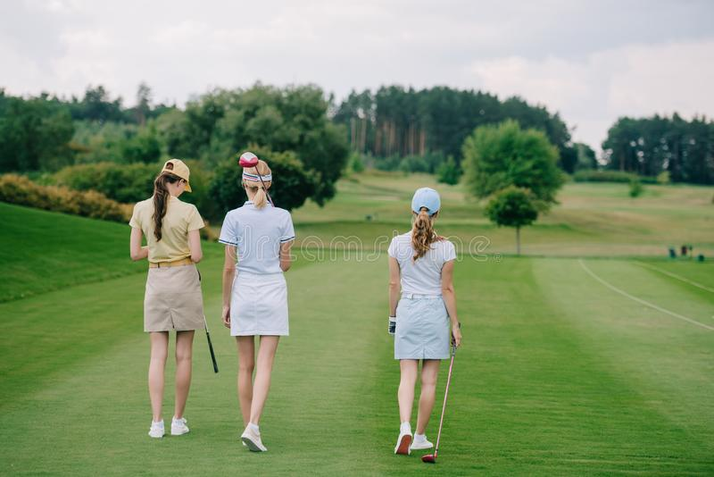 Rear view of women in caps with golf equipment walking. At golf course stock photo