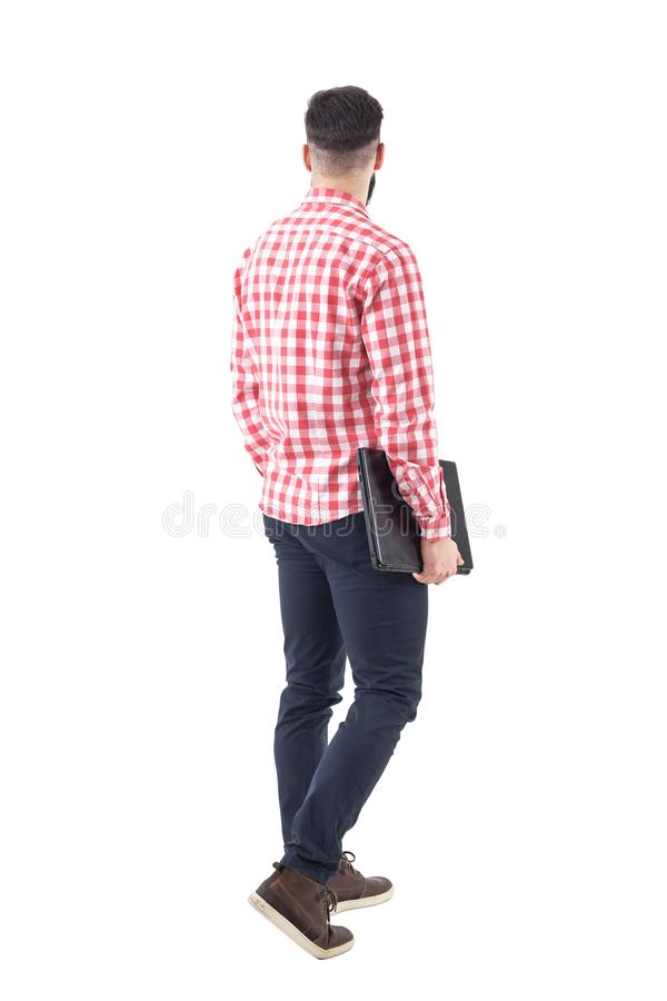 Rear view of young adult business man carrying laptop under arm walking and looking away. Full body isolated on white background stock photography