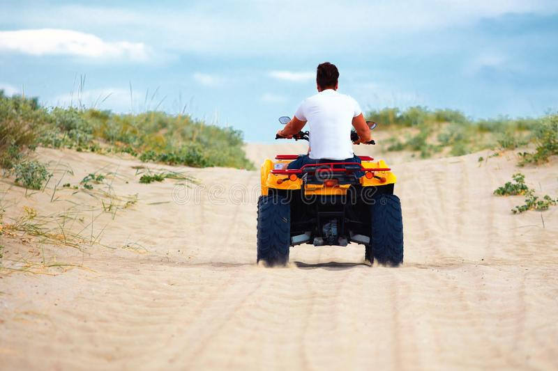 Rear view of man riding atv quad bike at sandy beach, summer vacation sport royalty free stock images