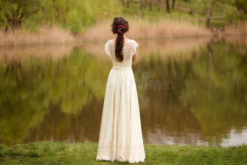 Rear view of a young anonymous bride in a beautiful full wedding dress, with hairstyle, looking down, nature background. stock images