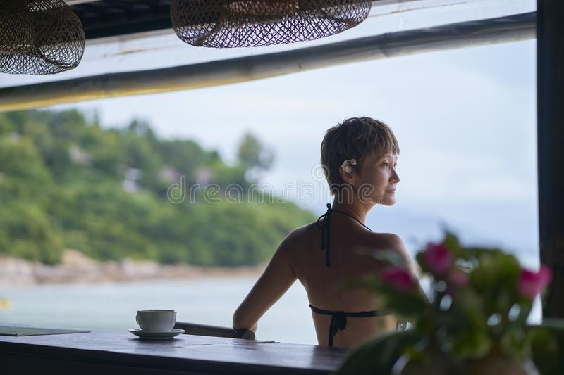 Rear view of young Asian beauty sitting, relaxing at beach bar in vacation. Rear view of young Asian beauty sitting alone, relaxing at beach bar in vacation stock photo