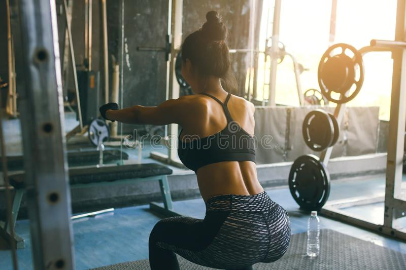 Rear view of young asian woman in sportswear doing squat at health club.  stock photos