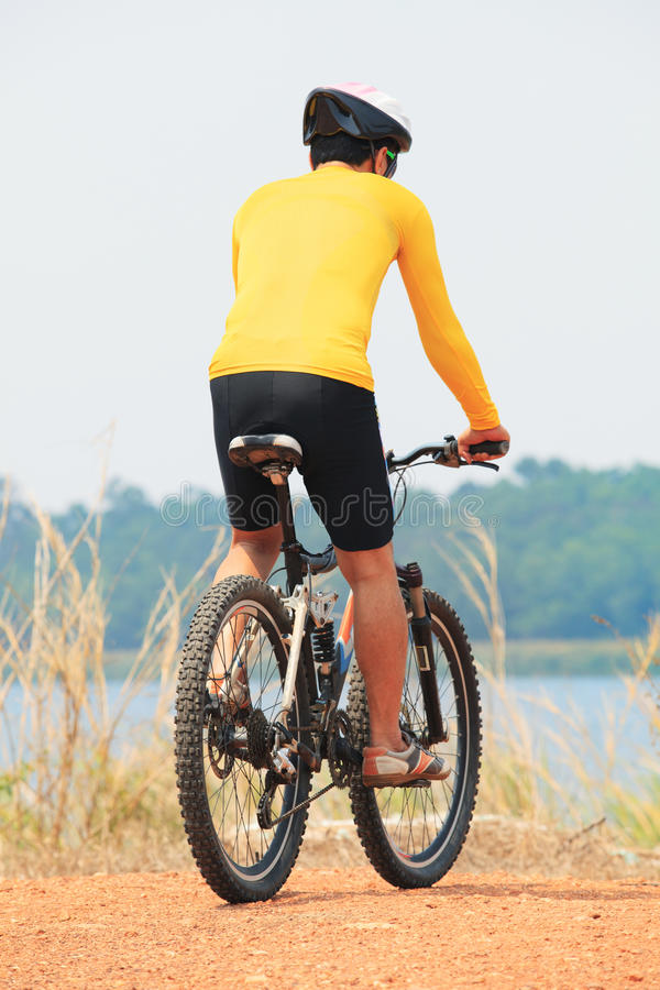 rear view of young bicycle man wearing rider suit and safety helmet riding mountain bike on dirt ground use for man and male act royalty free stock photos