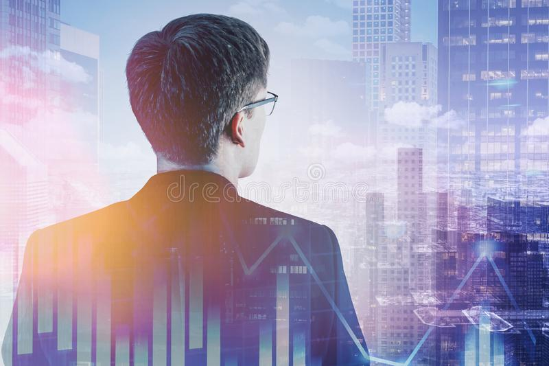 Man looking at city, digital graph. Rear view of young businessman in glasses looking at city with double exposure of digital graph. Concept of trading and stock stock photography