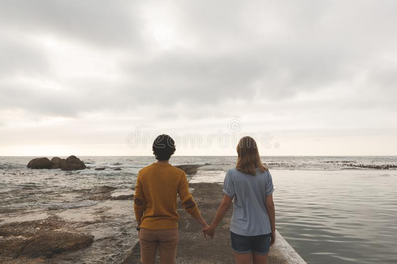 Caucasian couple standing on rock near beach stock photos