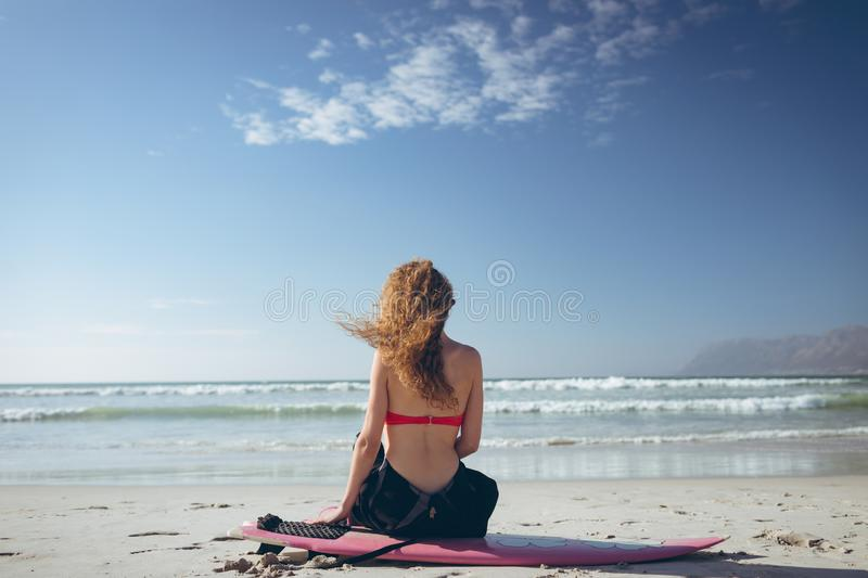 Female surfer sitting on surfboard at beach. Rear view of young Caucasian female surfer sitting on surfboard face to the ocean at beach on sunny day royalty free stock photo