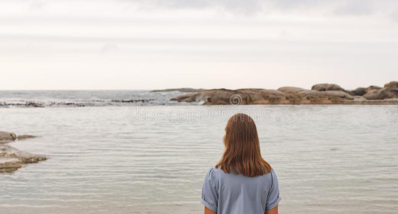 Young Caucasian woman standing at beach royalty free stock photos