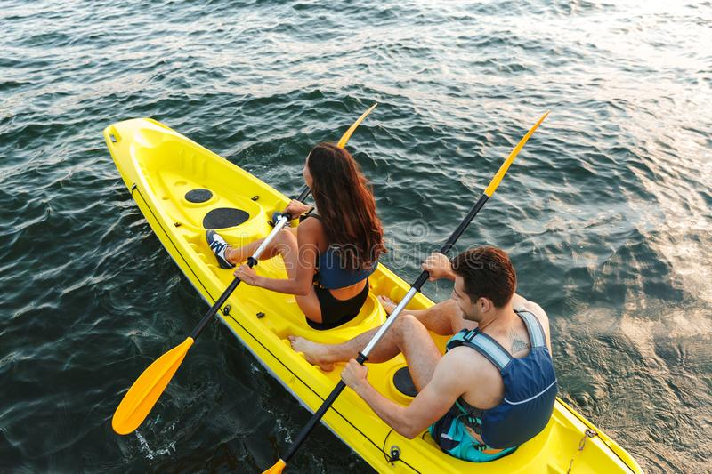 Rear view of a young couple kayaking on lake royalty free stock images
