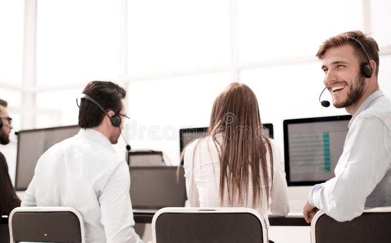 Rear view. young customer service agent sitting at his Desk royalty free stock photos