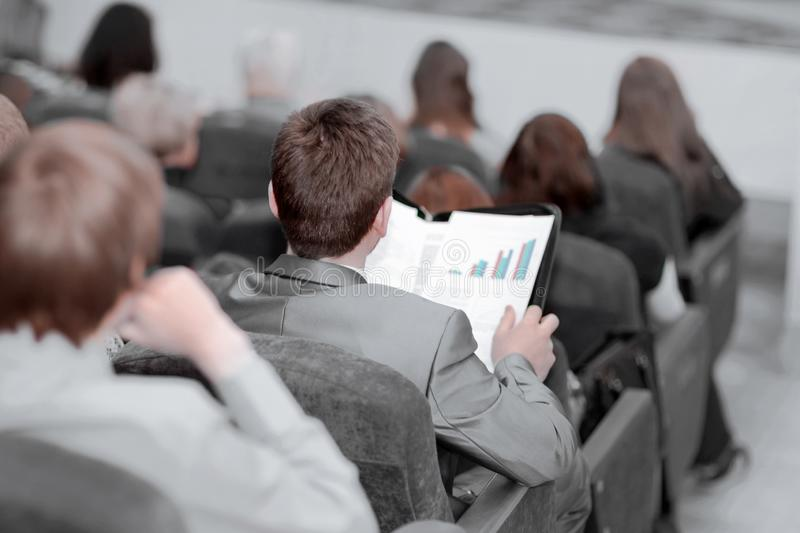 Rear view. young entrepreneurs listen to the speaker at the business conference royalty free stock image