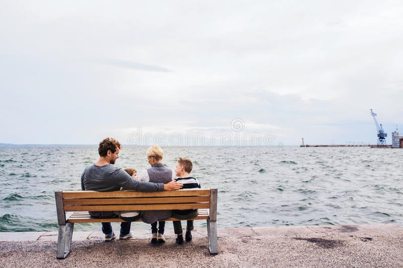 Rear view of young family with two small children on bench outdoors on beach. royalty free stock image