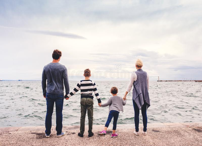 Rear view of young family with two small children standing outdoors on beach. stock photos
