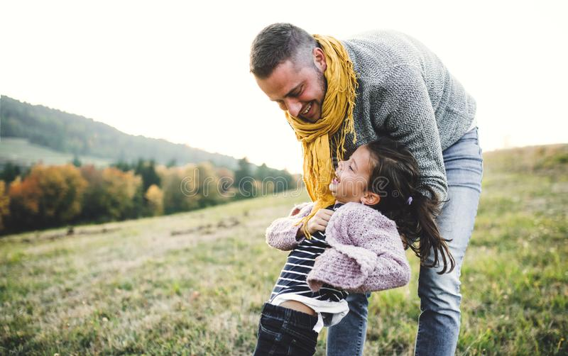 A rear view of young father having fun with a small daughter in autumn nature. royalty free stock photos